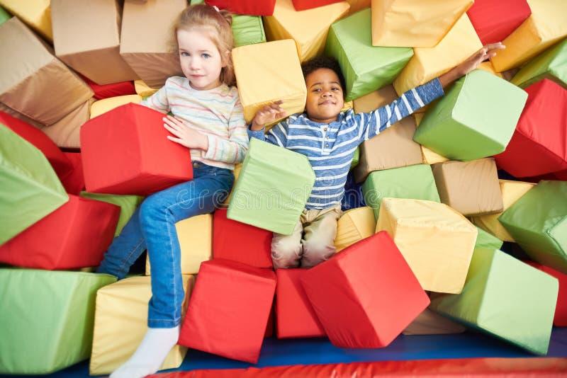 Niños que juegan en hoyo de la espuma fotos de archivo