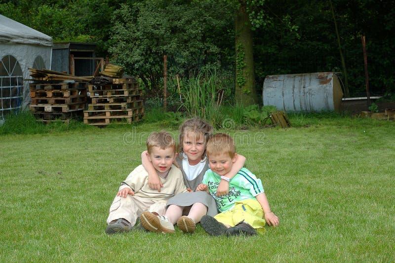 Niños que juegan en jardín. imagenes de archivo