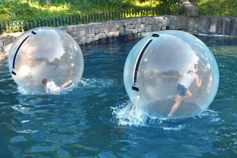 Niños que juegan en la bola del agua fotos de archivo libres de regalías