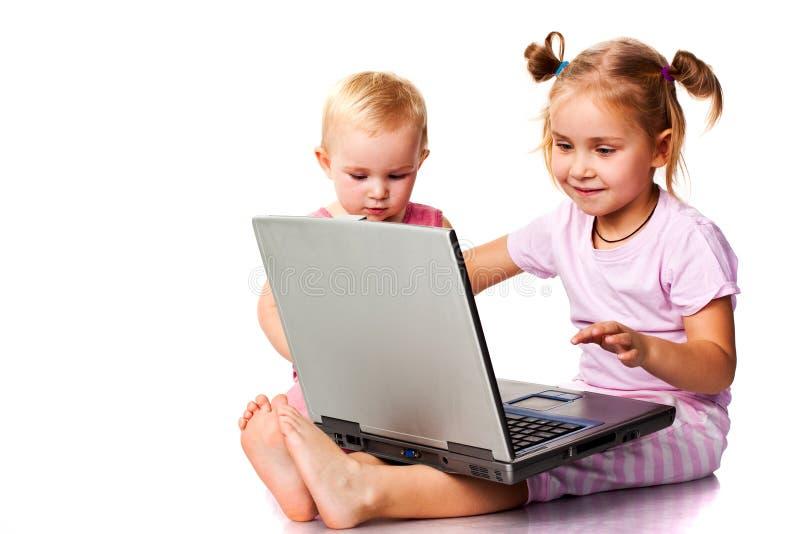Niños que juegan en la computadora portátil fotos de archivo