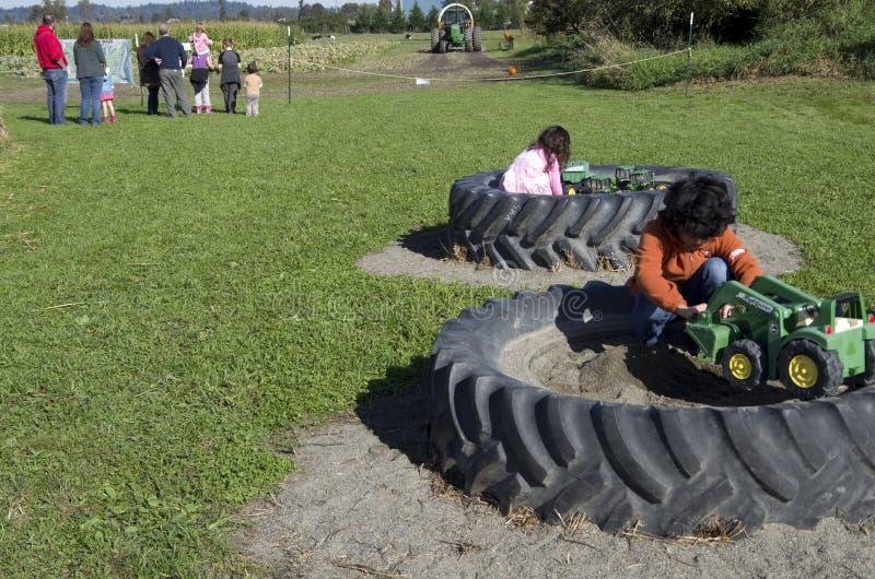 Niños que juegan en la granja de la calabaza imagenes de archivo