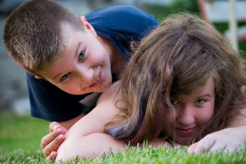 Niños que juegan en la hierba fotografía de archivo libre de regalías
