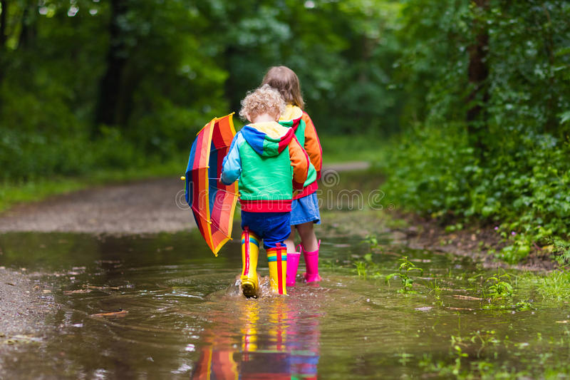 Niños que juegan en la lluvia con el paraguas imagenes de archivo