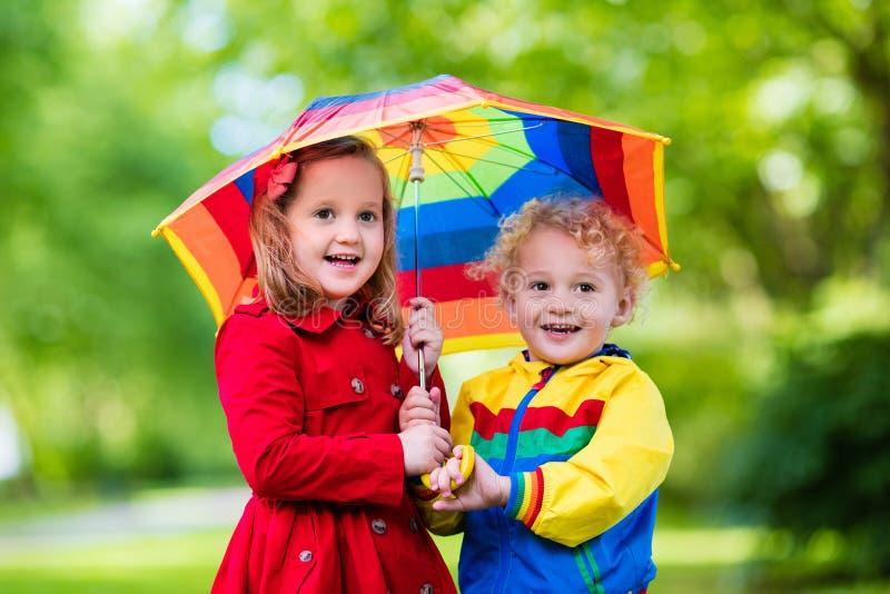Niños que juegan en la lluvia debajo del paraguas colorido foto de archivo libre de regalías
