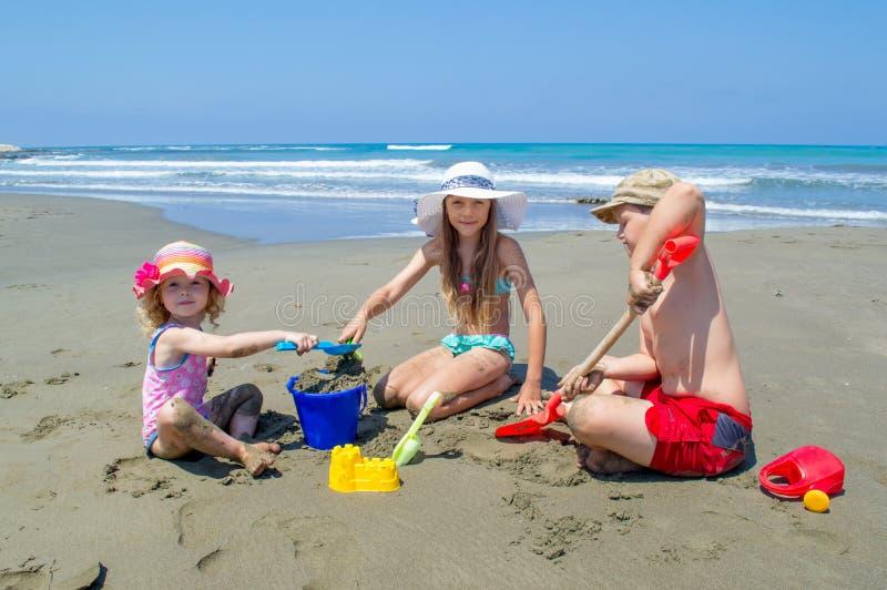 Niños que juegan en la playa imagenes de archivo