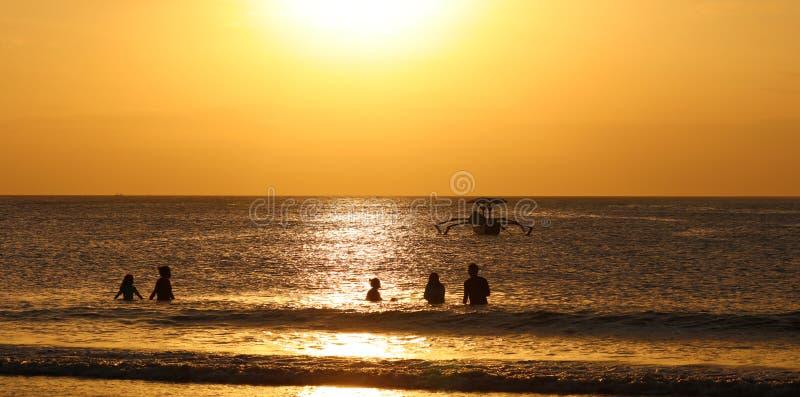 Niños que juegan en la playa con el barco en Bali, Indonesia del pescador durante puesta del sol en la playa foto de archivo