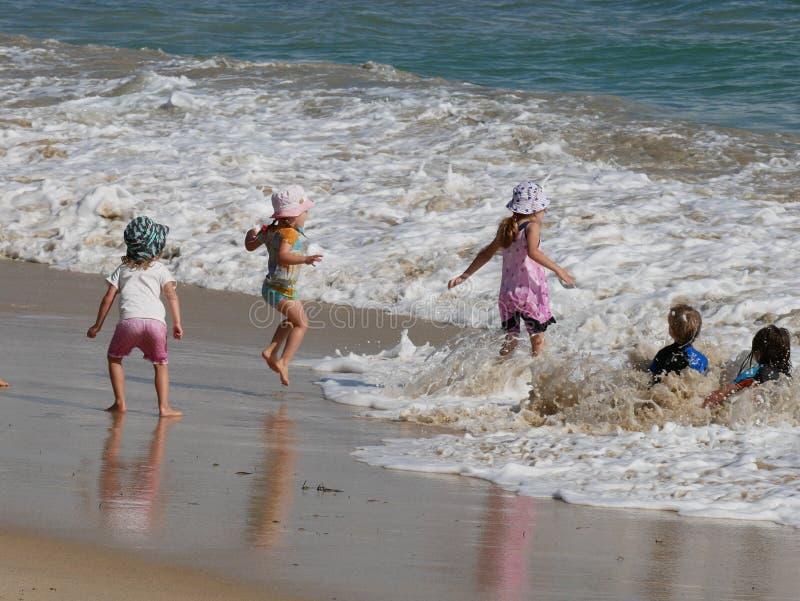 Niños que juegan en la playa, días felices imagenes de archivo