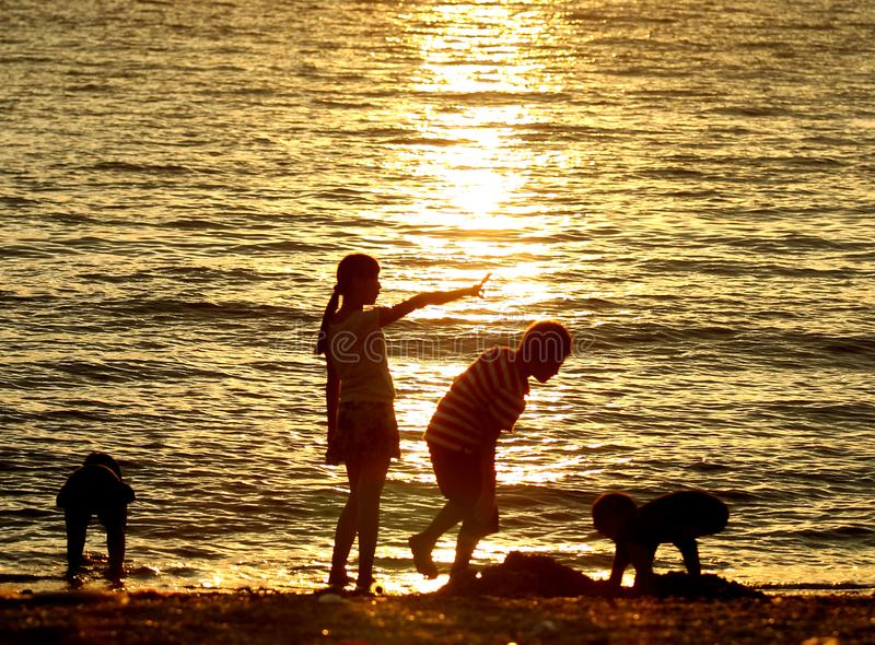 Niños que juegan en la puesta del sol en la playa fotografía de archivo