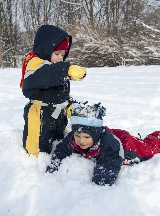 Niños que juegan en nieve imágenes de archivo libres de regalías