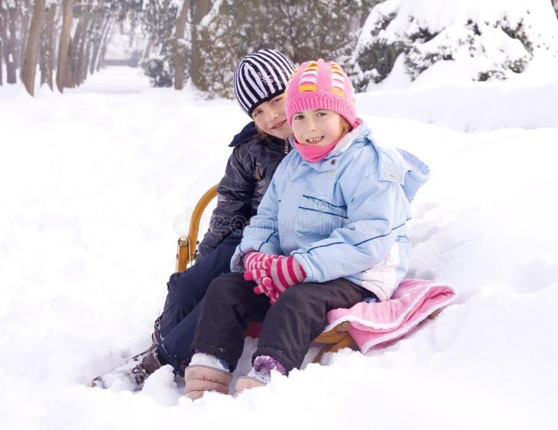 Niños que juegan en nieve imagenes de archivo