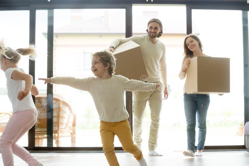 Niños que juegan en nuevo hogar, padres que sostienen las cajas, día móvil fotos de archivo libres de regalías