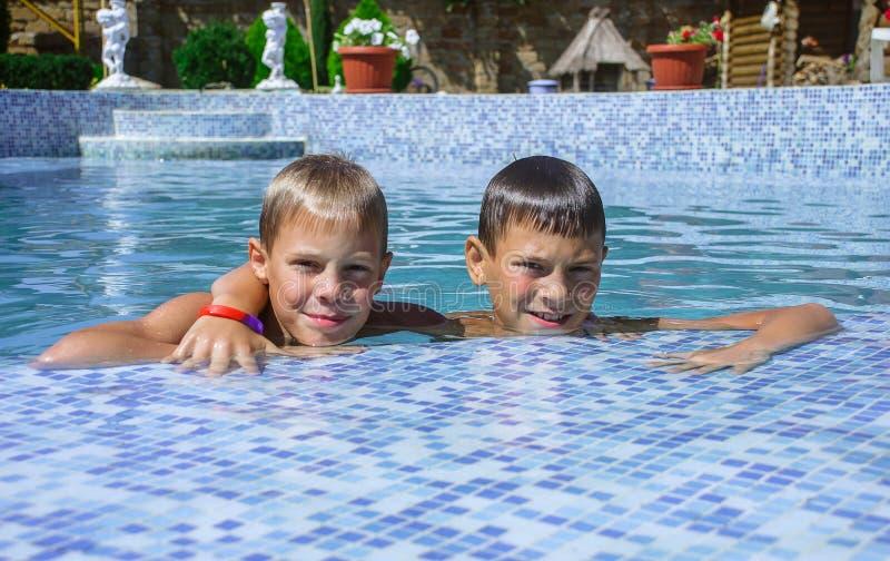 Niños que juegan en piscina imagenes de archivo