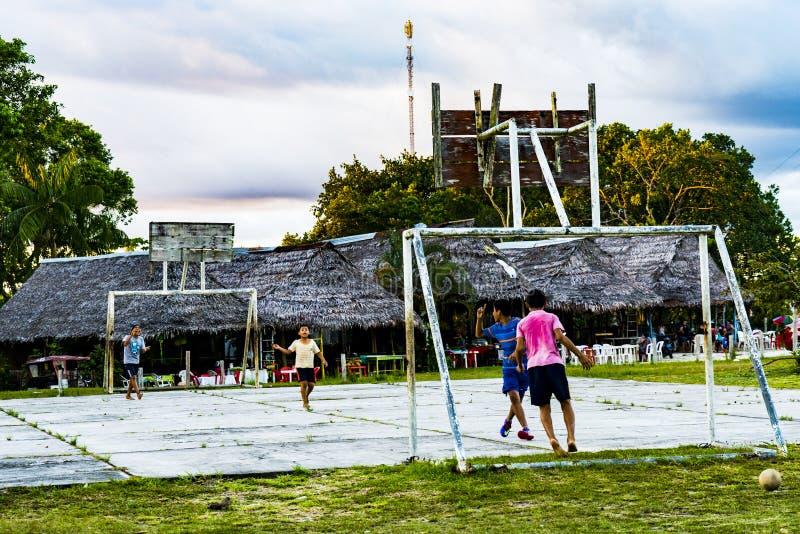 Niños que juegan a fútbol cerca de la selva tropical del Amazonas de Iquitos foto de archivo