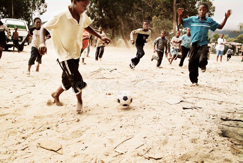 Niños que juegan a fútbol en el municipio, Suráfrica fotos de archivo