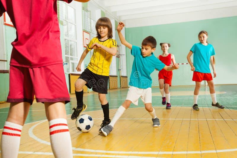 Niños que juegan a fútbol en gimnasio de la escuela fotos de archivo libres de regalías