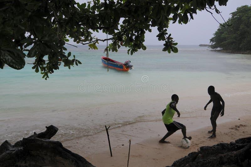 Niños que juegan a fútbol en la playa de Winnifred imagenes de archivo