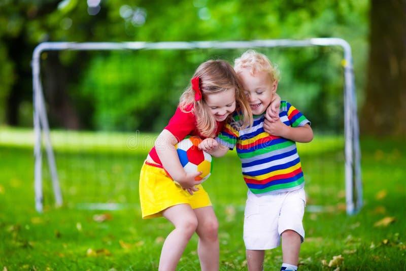 Niños que juegan a fútbol en un parque fotos de archivo libres de regalías