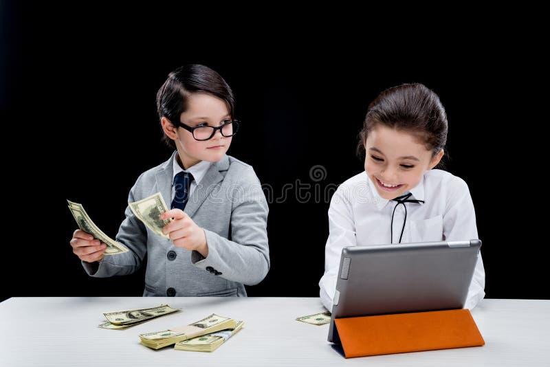 Niños que juegan a hombres de negocios con el dinero y el ordenador portátil imagen de archivo