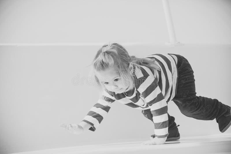 Niños que juegan - juego feliz Niño del niño pequeño que juega en el yate blanco foto de archivo