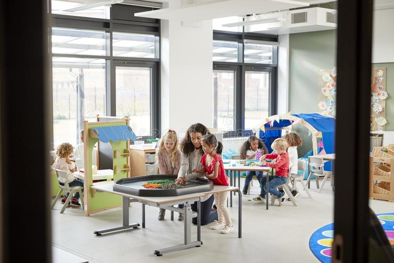 Niños que juegan a juegos con una maestra en una sala de clase en una escuela infantil, vista de la entrada imagenes de archivo