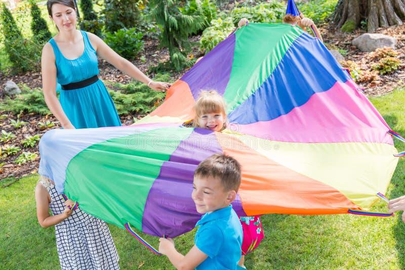 Niños que juegan a juegos del paracaídas foto de archivo