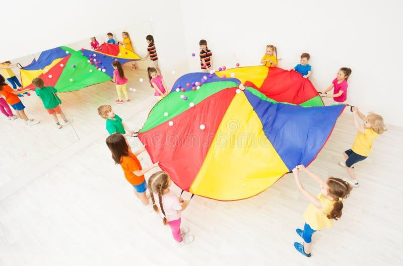 Niños que juegan a juegos del paracaídas en el pasillo de deportes de la escuela imagen de archivo libre de regalías