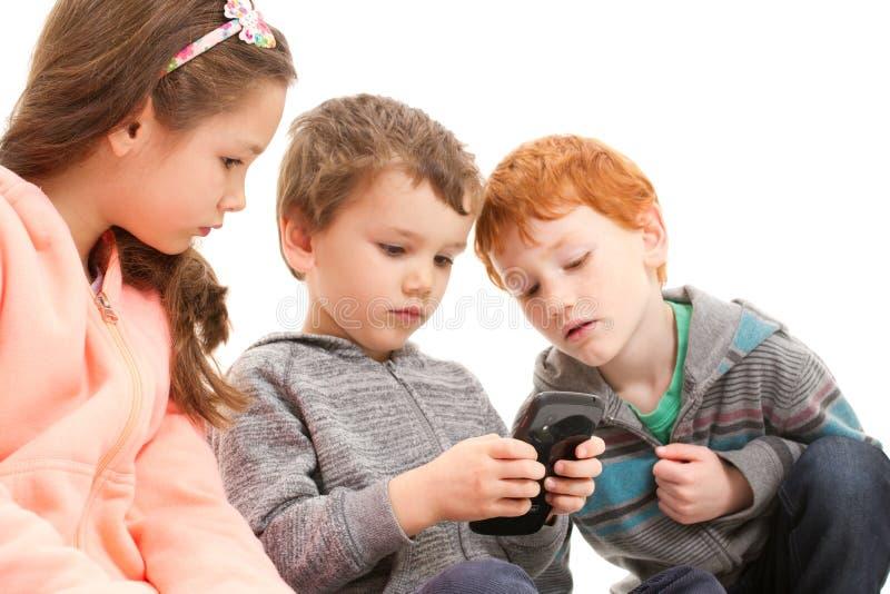 Niños que juegan a juegos en el teléfono móvil imagenes de archivo