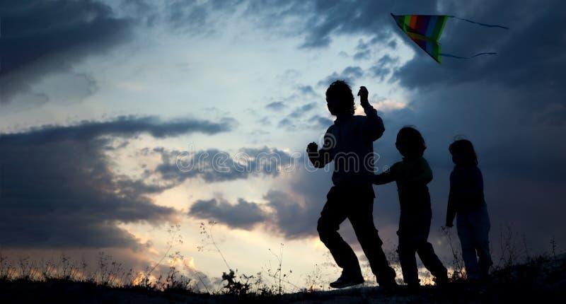 Niños que juegan la cometa en el prado de la puesta del sol del verano silueteado imagen de archivo
