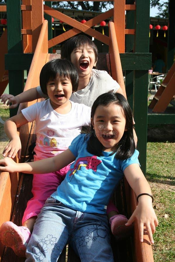Niños que juegan la diapositiva fotos de archivo
