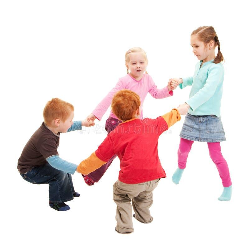 Niños que juegan las manos de la explotación agrícola del juego de los cabritos en círculo imagenes de archivo