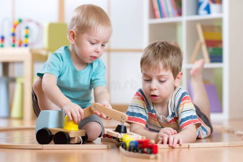 Niños que juegan los juguetes del ferrocarril y del coche en sala de juegos imágenes de archivo libres de regalías