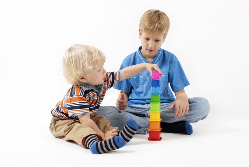 Niños que juegan los juguetes educativos imagenes de archivo