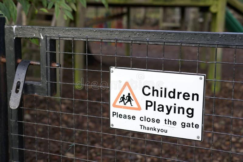Niños que juegan por favor la muestra cercana de la puerta en el parque del patio al aire libre foto de archivo