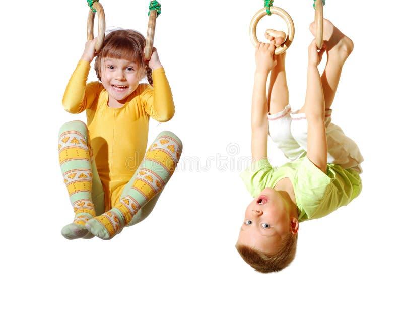 Niños que juegan y que ejercitan en los anillos gimnásticos imagen de archivo