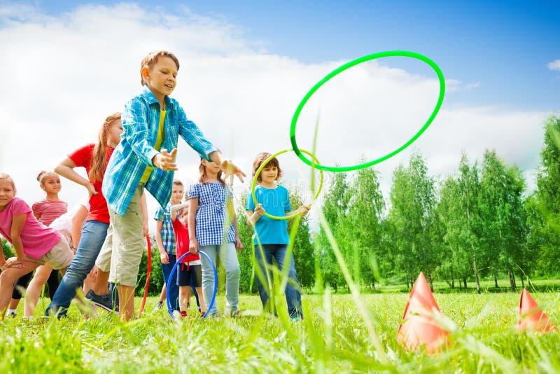 Niños que juegan y que lanzan aros coloridos foto de archivo libre de regalías