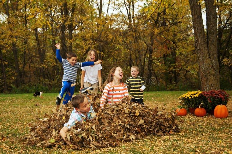 Niños que juegan y que saltan en hojas imagenes de archivo