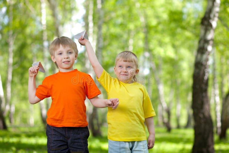 Niños que juegan y que vuelan un aeroplano de papel foto de archivo libre de regalías