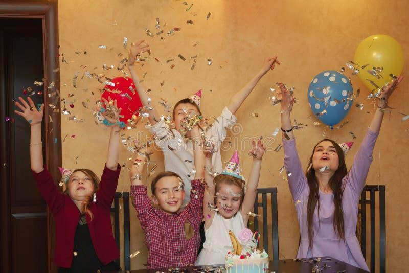 Niños que lanzan confeti en un children& x27; partido de s los niños se divierten junto en un día de fiesta de la familia imagen de archivo libre de regalías