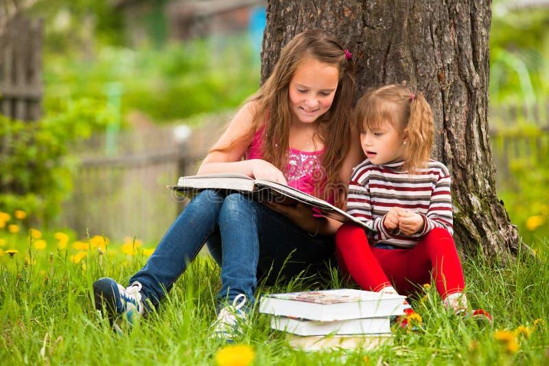 Niños que leen el libro imagenes de archivo