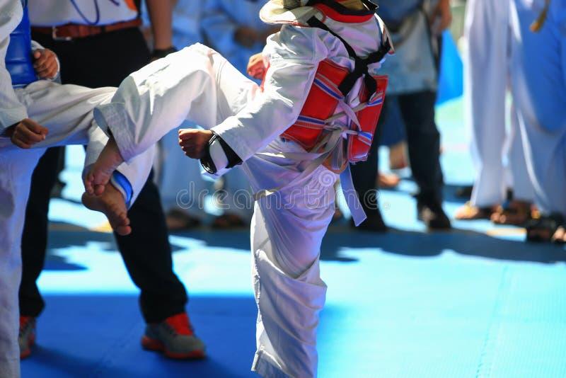 Niños que luchan en etapa durante la competencia del Taekwondo foto de archivo libre de regalías