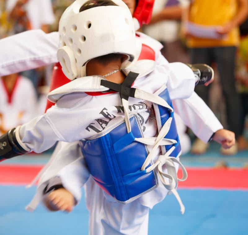 Niños que luchan en etapa durante la competencia del Taekwondo imagen de archivo