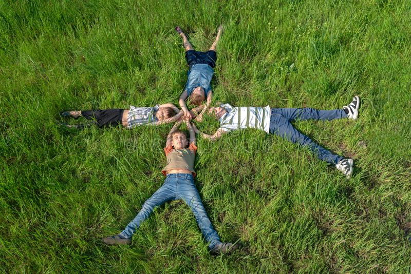 Niños que mienten en la hierba, los hermanos felices y alegres y las hermanas, visión superior imagen de archivo