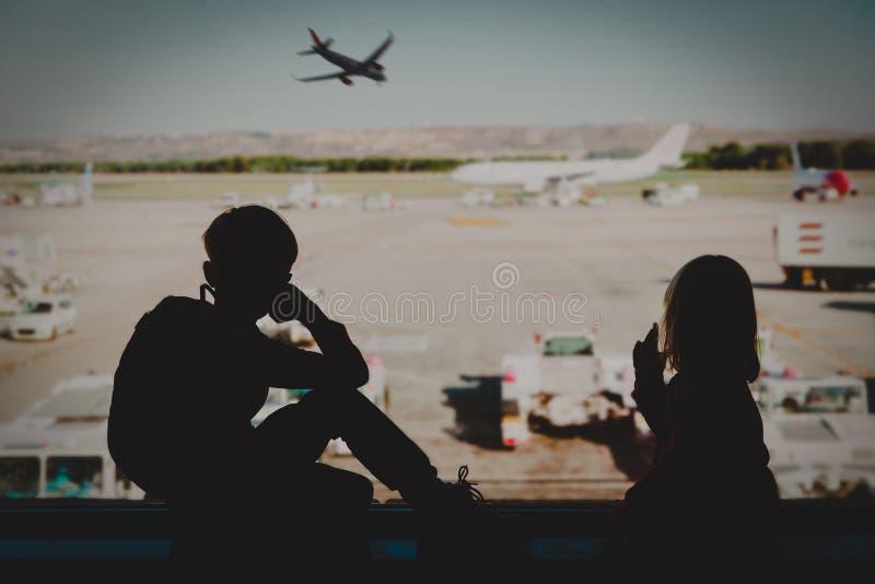 Niños que miran el avión en aeropuerto, viaje de la familia imágenes de archivo libres de regalías