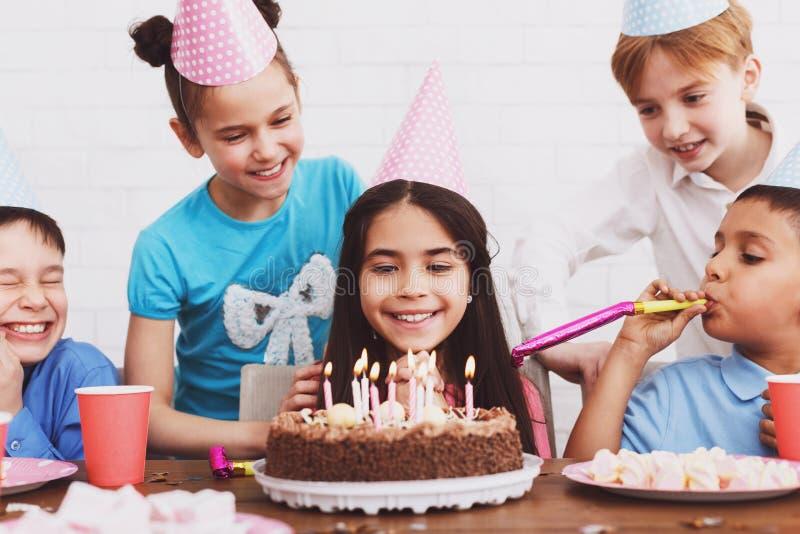 Niños que miran la torta de cumpleaños con las velas fotografía de archivo