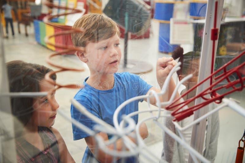Niños que miran a través del vidrio un objeto expuesto de la ciencia, cierre para arriba foto de archivo libre de regalías