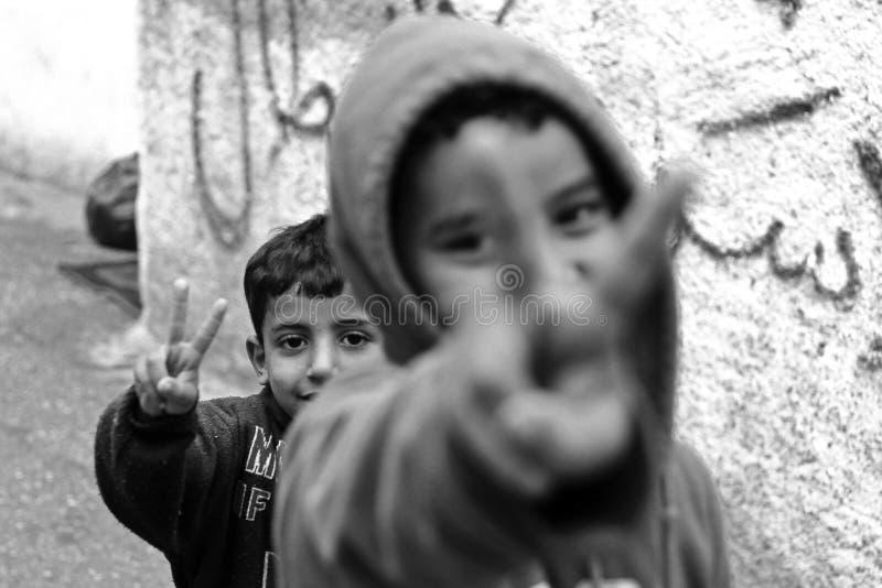 Niños que muestran el signo de la paz en el campamento de refugiados Aida en Palestina fotografía de archivo
