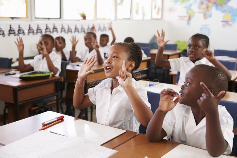 Niños que muestran las manos durante una lección en una escuela primaria fotografía de archivo