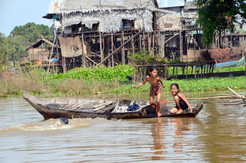 Niños que nadan en las aguas vergonzosas del río Tonle Sap, saltando del barco foto de archivo
