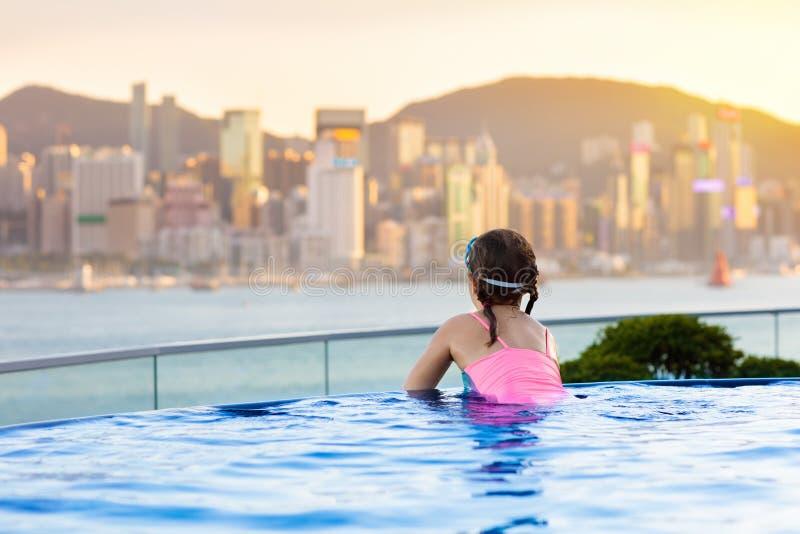 Niños que nadan en piscina al aire libre del top del tejado el vacaciones de familia en Hong Kong Horizonte de la ciudad de la pi imágenes de archivo libres de regalías