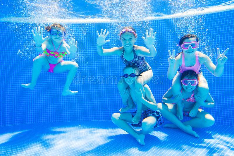 Niños que nadan en piscina bajo el agua imagenes de archivo